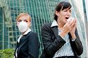 Picture of business woman sneezing, while another woman wearing a surgical mask looks on.